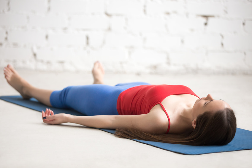 Beautiful happy young woman in bright sportswear working out indoors in loft interior on blue mat. Girl lying in Shavasana (Corpse or Dead Body Posture), resting after practice, meditating, breathing